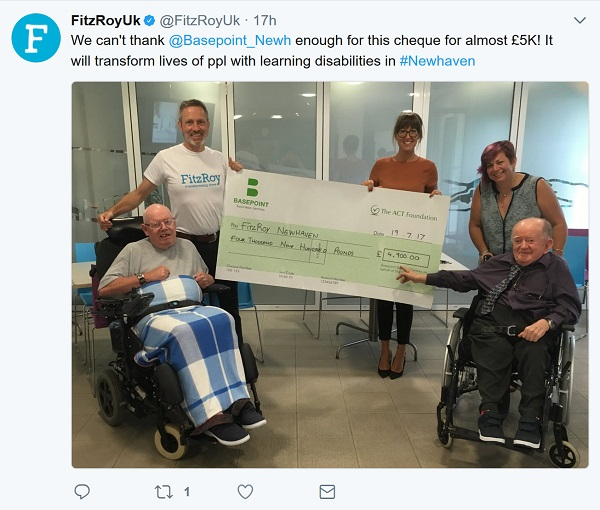 Cheque picture includes two people in wheelchairs as well as three others holding the giant cheque