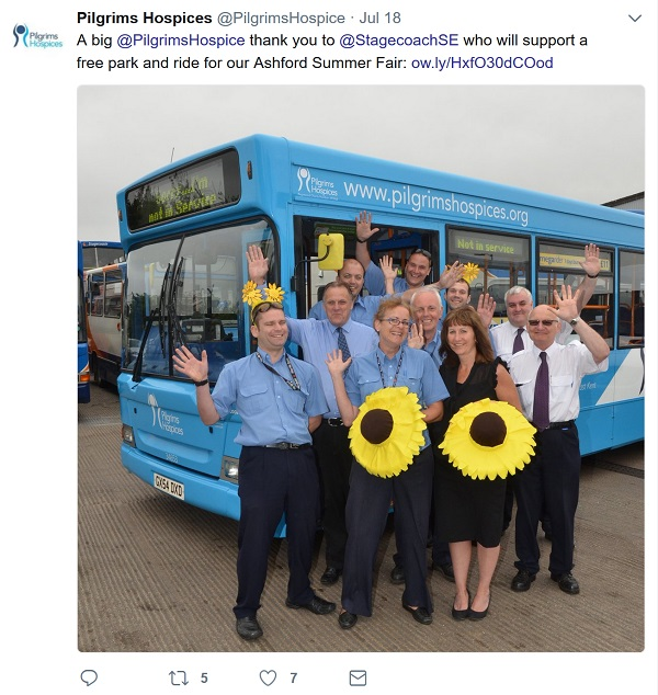 Smiling and waving staff in front of a bus with giant sunflowers