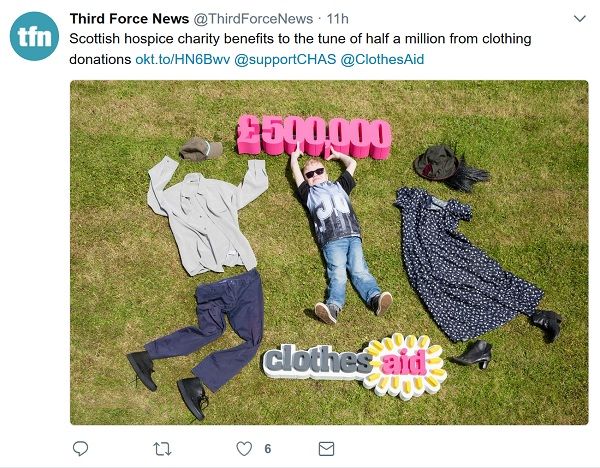 CHAS - clothes laid out on the grass, in the middle is a child holding the numbers £500,000