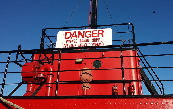 red boat. blue sky. sign saying: DANGER. intense sound signal operates without warning