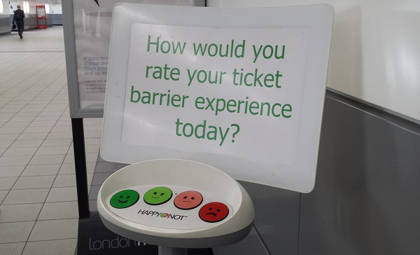Sign: how would you rate your ticket barrier experience today?' in a train station - 4 button choices