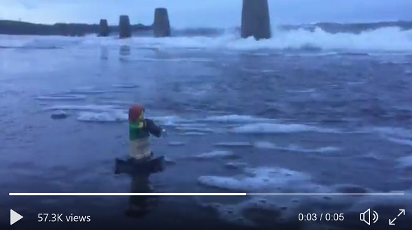 5s video showing a small wave washing away a person (in lego) talking a photo of the weather.