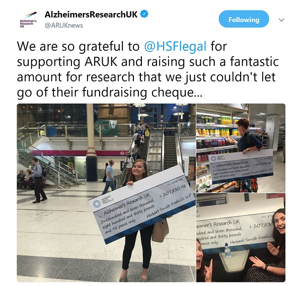 Tweet from Alzheimer's Research UK showing staff members out and about with a giant cheque. At the station. At the supermarket.
