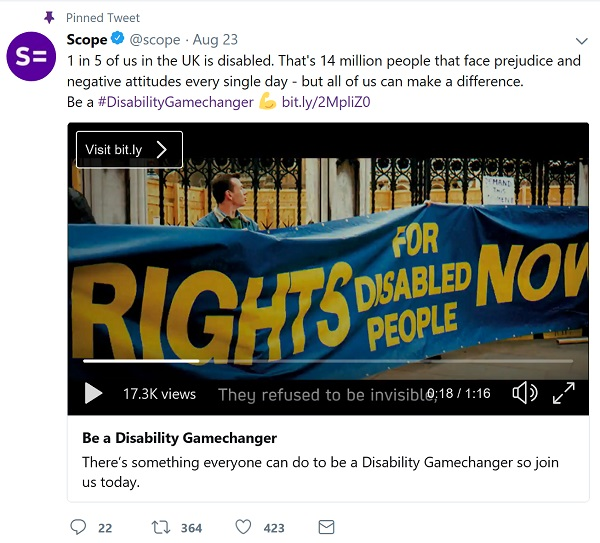 Still from Scope's video. Shows people walking with giant banner saying 'rights for disabled people'