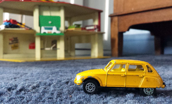 vintage toy yellow citron car on a fluffy blue carpet
