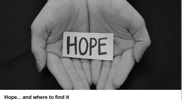 black and white photo of hands holidng a piece of paper with the word 'hope' written