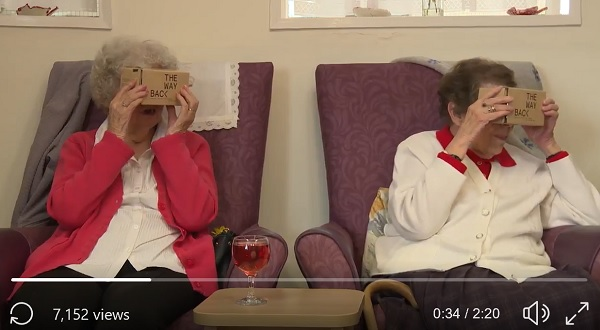 Still from Wayback video. Two older ladies using cardboard VR viewer, open mouths - wow!