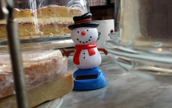 smiling windup snowman toy on a cafe counter surrounded by cakes