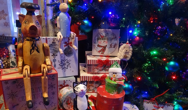 shop window dressed for Christmas with toys and a tree lit up (at night)