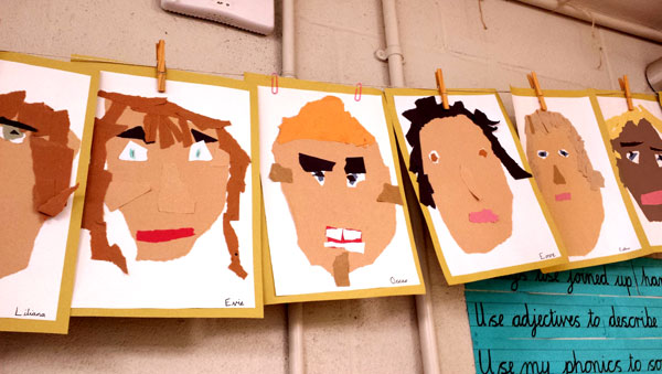 children's self portraits hanging in a classroom
