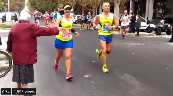 screenshot of video shared by Age UK of older lady standing next to runners in a race. She holds out her arm to get high fives from friendly runners.