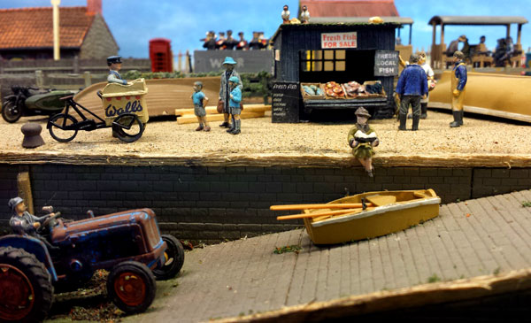 model of 1950s seaside. woman sits reading a book while two boys queue for ice cream