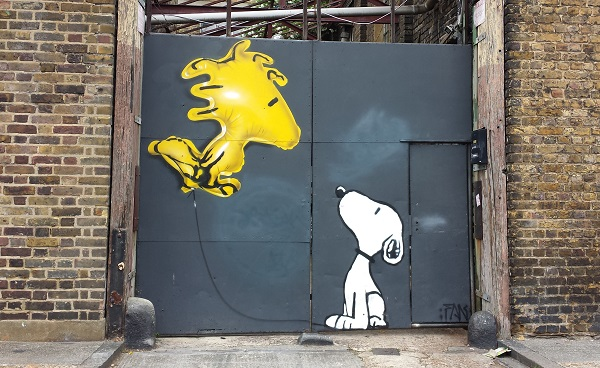 urban street art - snoopy the dog looks up at a flying yellow woodstock (from Charlie Brown)