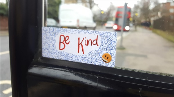Sticker on a bus stop says 'Be Kind'