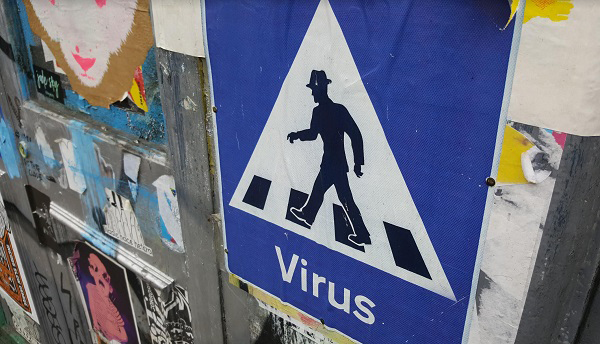Street art - Triangle with man in a hat walking across a zebra crossing. Says 'Virus' underneath. Looks like a warning sign.
