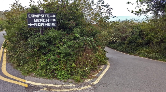 Handwritten sign points one way to campsite and beach, and the other to 'nowhere'!