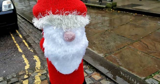 Yarn-bombed santa on a bollard. Photographed on a rainy street last year